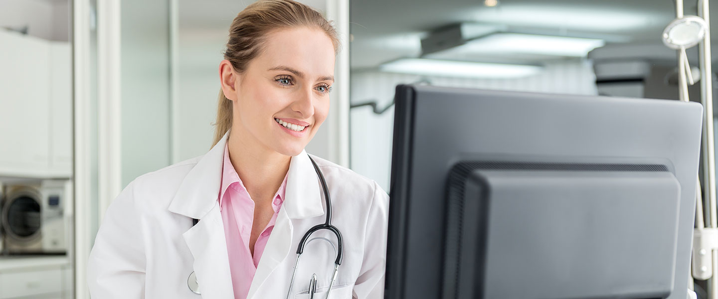 Female doctor at computer smiling looking at monitor